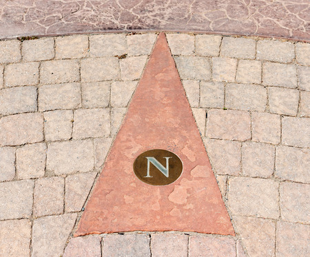 embedded: Pavement arrow pointing north   North icon symbol with the letter N embedded in brick walkway.