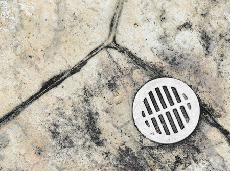 floor covering: Wet outdoor tile floor drain hole close up   Water draining down a metal drain cover grate embedded in the stone pavement.
