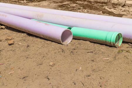 room for copy: Construction industry water pipes laying in the dirt   Plastic open pipe segments. Room for copy space.