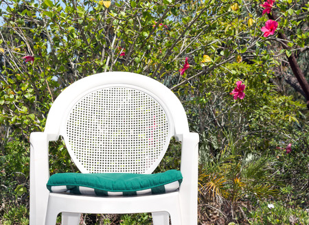 patio chair: Relaxing in the garden with white plastic patio chair   Front view of outdoor garden chair with green cloth seat cusion. Foliage and flower background.