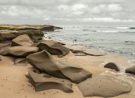 breaking waves: Low tide beach rock formation seascape with overcast sky   Natural smooth rocks in brown wet sand. Sea green water and sky colors. Breaking waves, birds, and clouds in background.