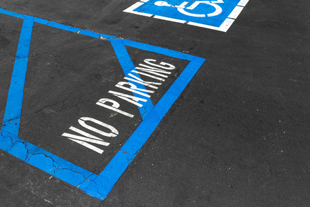 disabled parking sign: Handicapped reserved parking area with no parking white painted letters and blue diagonal lines on black asphalt   Rough cracked pavement. Wheelchair symbol in background. Room for text.