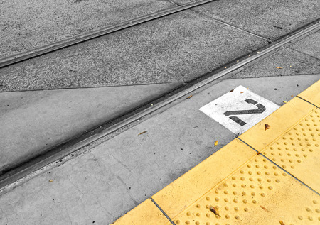 tactile: Waiting for the train   Light rail train station numbered platform with yellow tactile paving and train rails.