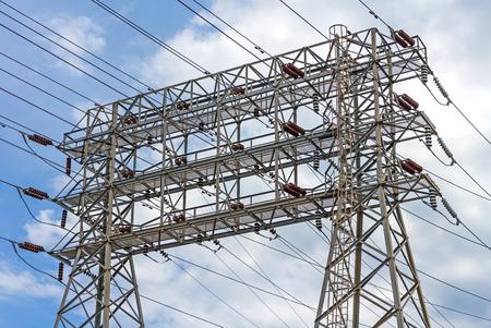 electricidad industrial: El poder de la industria eléctrica y energía torre de transmisión o torre de electricidad de celosía de acero estructura de rejilla de matriz de alambres, conductores y aislantes. Cielo azul y nubes de fondo. Foto de archivo