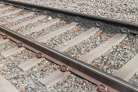ballast: Light rail train tracks and ties over small rocks ballast   Close up diagonal direction view showing concrete ties and metal rails. Stock Photo