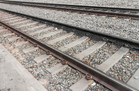 ballast: Two sets of  train tracks and ties over small rocks ballast   Close up diagonal direction perspective view showing concrete ties and metal rails. Stock Photo