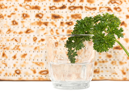matzah: Passover holiday fresh green parsley and saltwater in clear glass with blurred matzah background   Part of the seder ritual is dipping parsley, known in Hebrew as karpas, in saltwater. Isolated with copyspace.