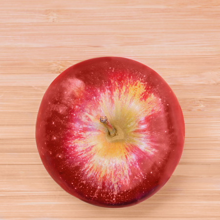 red square: Ripe whole red apple on light wood grain background top down view   Soft drop shadow with natural light and dark wood shading. Square composition. Bright red color.