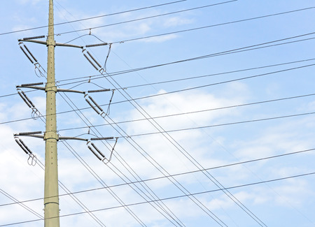 criss: Electric industry power and energy transmission tower or electricity pylon structure   Array of overhead criss crossed wires, conductors and insulators. Blue sky and clouds background. Stock Photo