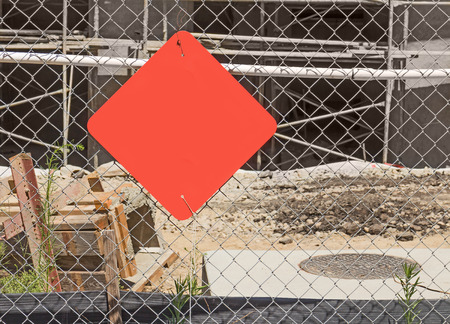 diamond shape: Construction site red blank warning sign hanging on wire chain link fence   Scaffolding, wood, and dirt in blurred background. Diamond shape sign with copyspace.