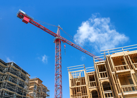 tilted view: Large tower crane and new unfinished residential townhouse construction, tilted buildings perspective   View from under the crane. Urban development theme. Blue sky and cloud background. Stock Photo