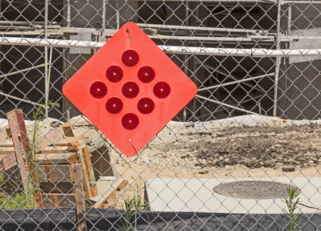 mesh: Construction site warning red reflector sign hanging on wire chain link fence   Scaffolding, wood, and dirt in blurred background. Diamond shape sign with round reflectors.