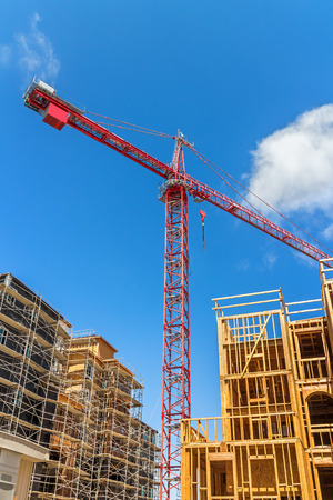 tilted view: Large tower crane and new unfinished residential townhouse construction, tilted buildings perspective   View from under the crane. Urban development theme. Blue sky and cloud background. Vertical composition.