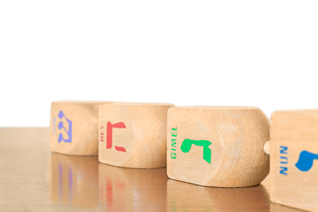 hebrew letters: 4 Chanukah wooden dreidels in a row laying on a wood surface.  Large dreidels with Hebrew letters nun, gimel, hey, shin. Shallow depth of field, drop shadow. Selective focus on the winning letter gimel. Copyspace. Isolated on a white background.