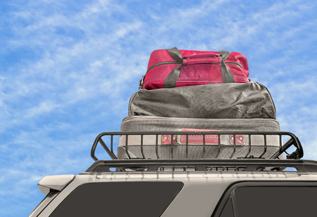 duffle: Luggage on van roof rack.   Cloth suitcase and duffle bags on top of minivan metal carrier. Blue sky and clouds background. Stock Photo