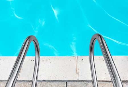 handrails: Swimming pool metal handrails and stone tile edge top down view .   Calm blue water ripples. Copyspace. Stock Photo