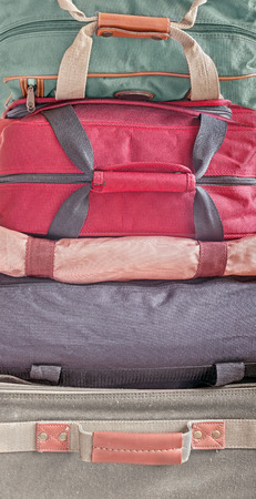duffle: Stack of luggage.   Front view of small cloth suitcase and nylon duffle bags piled high. Tightly cropped vertical image. Stock Photo