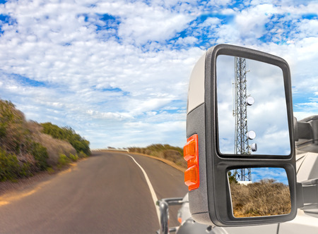 wireless connection: Cellphone communication tower reflection in truck side rear view mirror.   On the road motion blur, rural area, blue sky with clouds background. Wireless connection to the internet anywhere concept. Stock Photo