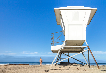 view from behind: View from behind the tall lifeguard tower overlooking the calm ocean horizon, wide angle perspective.