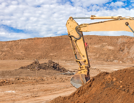 dirt pile: Construction excavator boom, arm, and bucket with pile of dirt.  Blue sky and clouds background.