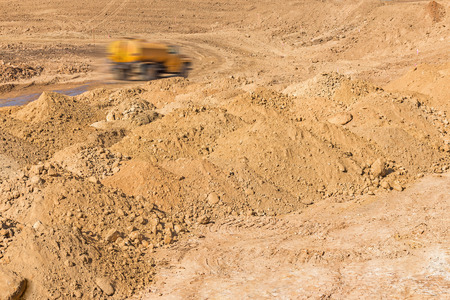 mounds: Construction site mounds of dirt and rock.  Moving water truck with motion blur in background.