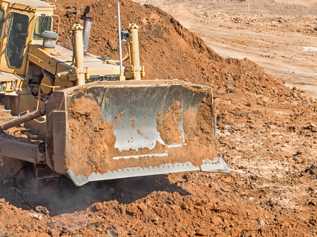 dirt pile: Construction bulldozer blade and pile of dirt .  Heavy equipment earth mover kicking up dust and pushing dirt around.