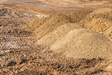mounds: Construction site small mounds of dirt and rock.  Dirt neatly piled to the side of the work area. Stock Photo
