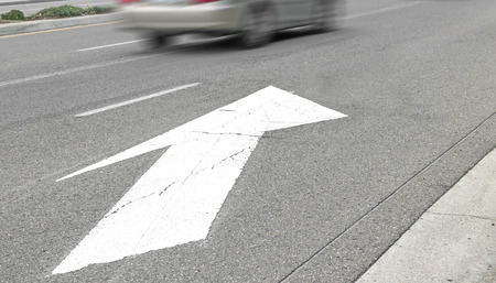 merging: Road marking white arrow on gray asphalt street surface.  Indicates traffic lanes merging. Fast moving car in background. Motion blur. Perspective view.