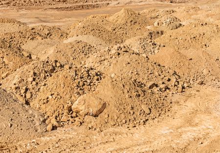 mounds: Construction site mounds of dirt and rock .  Reddish brown rust color soil.
