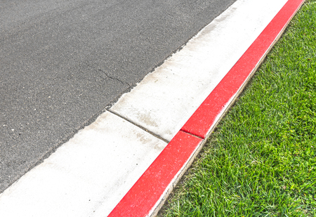 curb: Red painted curb bounded by grass and street.   Suburban bus stop or no parking red zone.