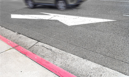merging: Road marking white arrow on gray asphalt street surface.  Indicates traffic lanes merging. Fast moving car in background. Motion blur. Stock Photo