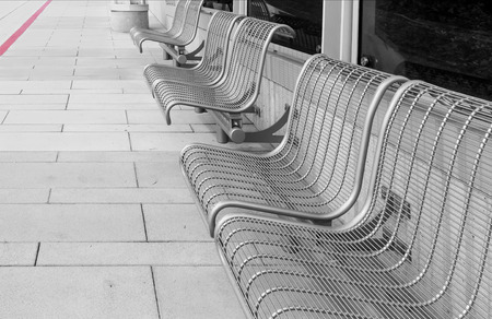 bolted: Row of empty seats at bus stop.  Gray metal frame chairs bolted to concrete wall and tile sidewalk. Red curb in background.