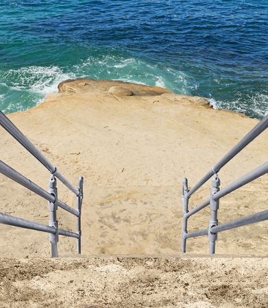 handrails: Stairway with metal handrails leading down to rocky edge by the ocean.  Blue green water and wave. Stock Photo