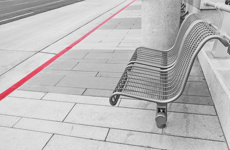bolted: Pair of empty seats at bus stop.  Gray metal frame chairs bolted to concrete tile sidewalk. Red curb and street in background.