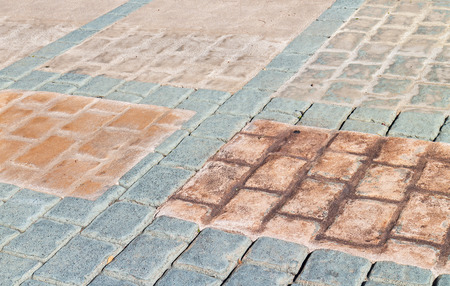 tile flooring: Outdoor walkway of multicolored stone tiles.   Ceramic tile flooring, square pattern with blue, orange, brown, and beige colors.