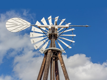 wind mill: Top of a wooden pump windmill with metal wind vane arrow.   Used for pumping water and finding wind direction. Fluffy clouds and deep blue sky background.