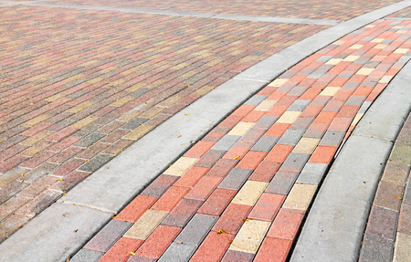 curving: Multicolor brick pedestrian walkway.  Curving path of red yellow orange and light blue color stone. Stock Photo