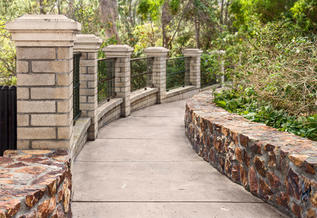 walkway: Paved garden walkway .  Curved path bordered by brick pillars, iron fence, and low stone wall. Blurred background. Stock Photo