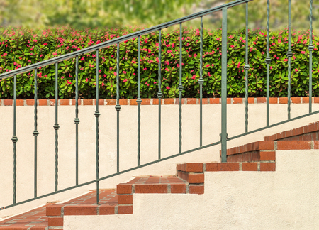 metals: Side view of outdoor brick stairs with metal railing, stucco wall and garden hedge background.  Bushes with green leaves and small pink flowers. Stock Photo