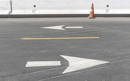 way: White traffic arrow road markings pointing in opposite directions on gray asphalt in parking lot construction area.   Yellow line separates driving lanes. White concrete wall, orange traffic cone in blurred background. Stock Photo