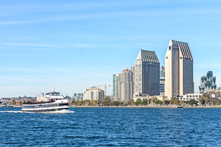 harbour: San Diego bay passenger ferry boat and city skyline during the day.   Downtown commercial buildings in background. Blue sky. Lots of copyspace. Stock Photo