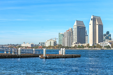 wood pillars: San Diego bay jetty and city skyline during the day.   Empty wood pier and metal walkway with concrete pillars extend into the blue water. Commercial buildings in background.