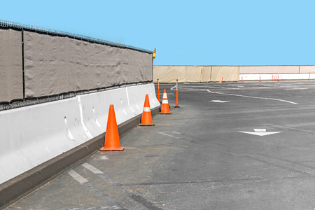 deserted: Construction fence and concrete wall, orange traffic cones in empty parking lot.   White traffic arrows indicate driving direction through the site. Clear blue sky. Copyspace.