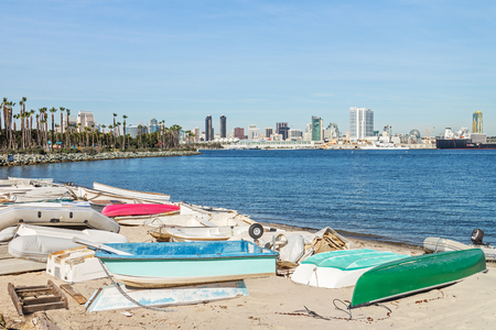 dinghies: Old small fishing boats on sandy shore of San Diego bay, southern California.   Weathered and dirty dinghies scattered across the sand. Downtown city skyline in the background. Stock Photo
