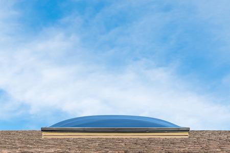 shingles: Perfil del exterior ventana cúpula lucernario en la parte superior del techo de tejas de color marrón. Poca profundidad de campo, bajo ángulo, vista lateral. Cielo azul y nubes tenues. Copyspace.