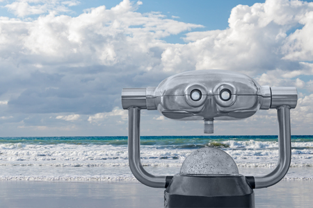 turn away: Outdoor daytime viewing telescope looking at foamy ocean waves, cloudy sky, and horizon.  Blurred background. Gray metal swivel scope with two eyepieces and focusing knob. Copy space.