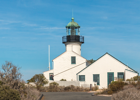 building structures: Old Point Loma lighthouse historic building and San Diego landmark.  Cape Cod style architecture. White wood and brick structures now used as a public museum. Fresnel lens visible in tower. Blue sky with hazy cloud background. Room for text, copyspace.