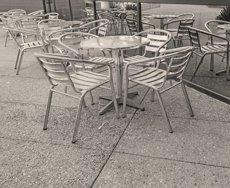 round chairs: Outdoor cafe tables and chairs with window reflection.  Small round metal tables and patio chairs. Black and white photo. Stock Photo