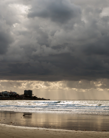 the backlighting: Stormy beach scene with sun rays streaming through heavy storm clouds.  High contrast backlighting, ocean waves, shimmering wet sand.