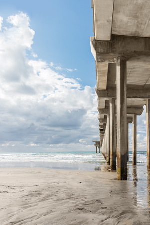 concrete structure: After the storm at Scripps Pier, La Jolla, San Diego, California.  Perspective view from under the concrete structure. Wet sand and heavy clouds. Vertical composition with cloudscape over the horizon.